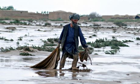 A man carries his belongings after floods devastated Jawzjan province and neighbouring Faryab province in Afghanistan. Photograph: Mustafa Najafizada/AP