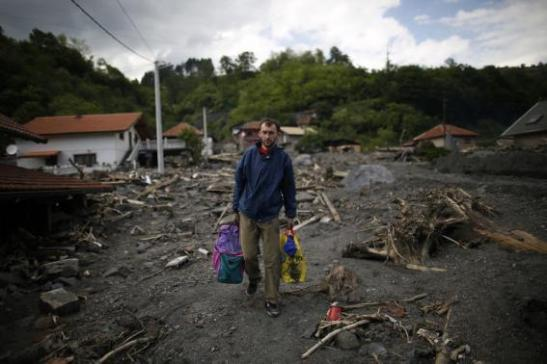 A man carries belongings recovered from his house Credit: Reuters/Dado Ruvic