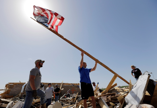 Justin Shaw, left, helps Nick Conway erect a flag pole at his home in Vilonia. AP Photo/Eric Gay