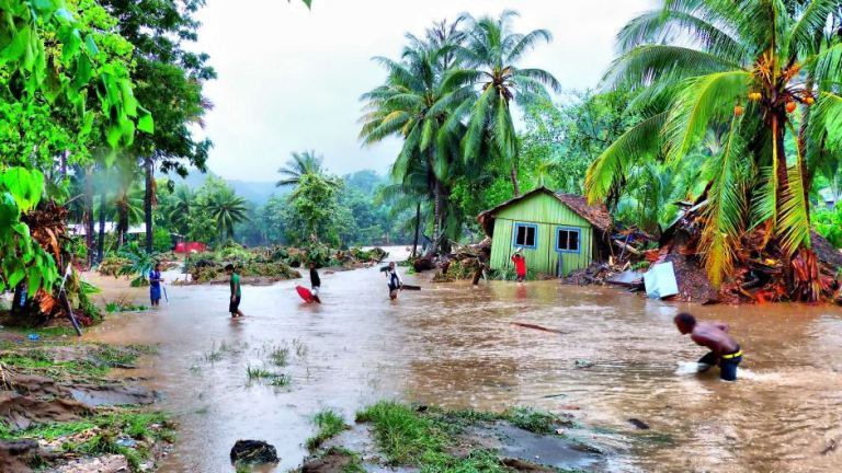 Locals walk through floodwaters after days of heavy rain in the Solomon Islands, which caused flash flooding and the Mataniko River in Honiara to burst its banks, April 4, 2014.