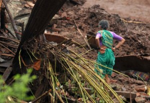 A resident looks at the debris of her damaged house after a landslide at Malin village in the western Indian state of Maharashtra July 30, 2014. REUTERS/Stringer