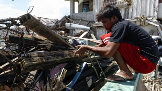 A man collects debris of houses and other structures felled by Typhoon Haiyan in the Philippines. Months since the supertyphoon hit the country, long-term rehabilitation that includes sustainable housing and livelihood remains to be seen. Photo by: Marcel Crozet / International Labor Organization / CC BY-NC-ND