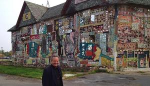 MinnPost photo by Beth Hawkins Photojournalist Bruce Giffin posing in front of the N'Kisi Iron House.