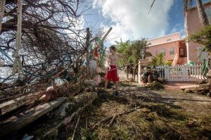 Stefano Ausenda cleared debris from his driveway in Sandys Parish on Saturday after Hurricane Gonzalo left a trail of destruction in western Bermuda. Credit Reuters