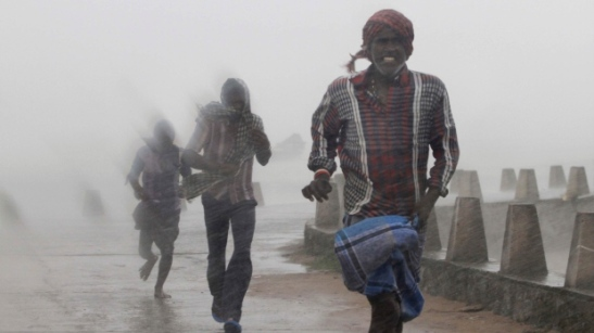 People run for shelter as heavy rain and wind gusts rip through the Bay of Bengal coast at Gopalpur, Orissa, about 285 kilometers north east of Visakhapatnam, India on Sunday, Oct. 12, 2014. (AP / Biswaranjan Rout)
