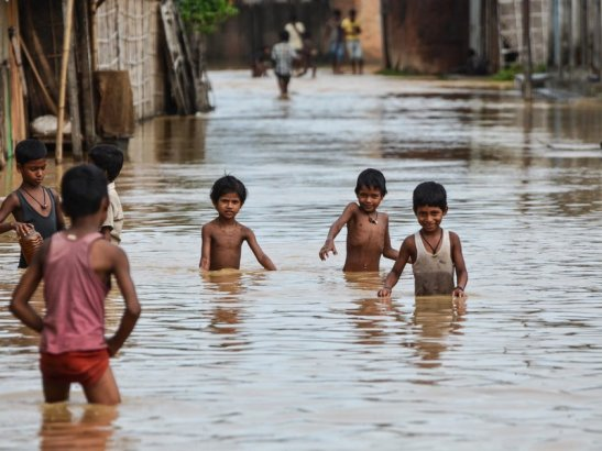 Children wade through flood waters in northern India in July 2013. (Caisii Mao/NurPhoto/Corbis