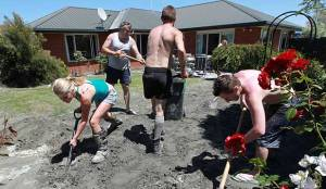 ESSENTIAL SUPPORT: Neighbours and friends help clear liquefaction at the Parklands home of Duncan Turner after the December 23, 2011 earthquake.