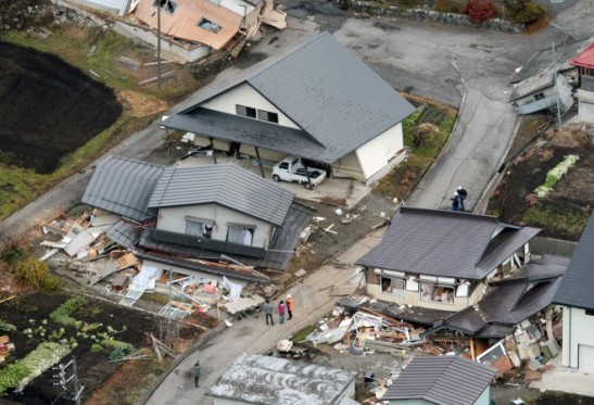 This aerial photo shows houses collapsed after a strong earthquake hit Hakuba, Nagano prefecture, central Japan, Sunday, Nov. 23, 2014. The magnitude-6.8 earthquake shook on Saturday night the mountainous area that hosted the 1998 Winter Olympics destroying more than half a dozen homes in the ski resort town and injuring at least 30 people, officials said. (AP Photo/Kyodo News)