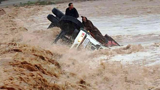 Drivers and a truck are stranded in flood waters November 22, 2014 2014 in the southern region of Ouarzazate in Morocco. (AFP)