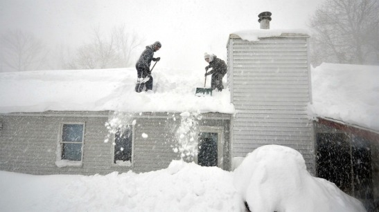 Tami Normile and Richard Brooks attempt to remove some of the 5 feet of snow from a rooftop on Nov. 20, 2014 in the Lakeview neighborhood of Buffalo, New York. Image: John Normile