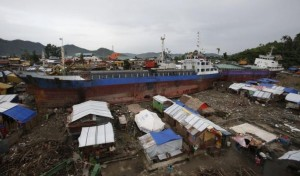 Typhoon survivors living in temporary shelters are seen near ships that ran aground, nearly 100 days after super Typhoon Haiyan devastated Tacloban city in the central Philippines, Feb. 14, 2014. REUTERS/Erik De Castro