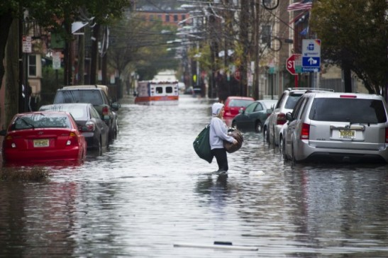 A woman walks through flood water and past a stalled ambulance in the aftermath of Superstorm Sandy in Hoboken, NJ. Oct. 30, 2012. (AP Photo/Charles Sykes, File)