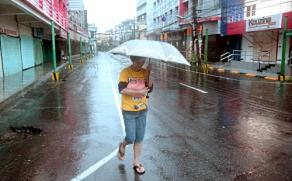 A resident braves strong rain as she walks along an empty street hours before Typhoon Hagupit passes near the city of Legazpi. Photo courtesy: AFP