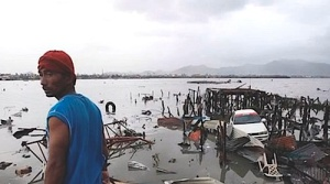 A resident of Tacloban in the Philippines surveys the damage after Typhoon Haiyan devastated the region in 2013. The storm displaced some 2 million people.