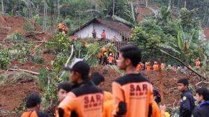 Rescuers search for the victims of a landslide that swept away a village in Jemblung, Indonesia. (AAP)