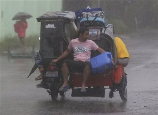 A resident rides a tricycle on the way to an evacuation center as strong winds and rains from Typhoon Hagupit hit Legazpi, Albay province, eastern Philippines on Sunday, Dec. 7, 2014. Aaron Favila/The Associated Press