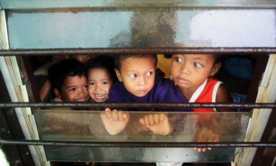 Children peer from a window inside a school turned into a temporary evacuation centre in Daanbantayan, Cebu province in central Philippines.