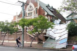 Photo: A cyclist rides past the West End Uniting Church that lost its roof in the storm that swept across Brisbane on November 27. (ABC News: Giulio Saggin)