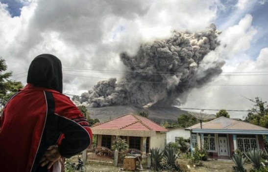 A woman in a village in Karo regency watches Mount Sinabung erupt in Indonesia's North Sumatra province, Oct, 8, 2014. REUTERS/YT Haryono