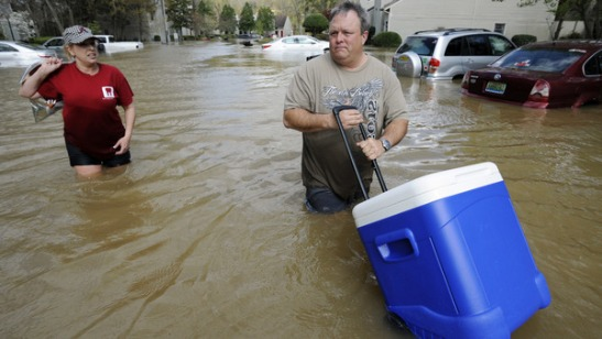 Last April, David Cowan uses a cooler to help Shannon Martin remove belongings from her flooded home in Pelham, Ala. Heavy rains sent a creek out of its banks and resulted in severe flooding in parts of central Alabama. (AP Photo/Jay Reeves)