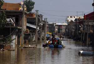 Men ferry flood victims on a makeshift raft in the flooded Bemina area of Srinagar. Tribune file Photos