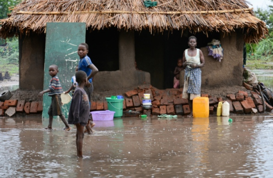 A family wait for relief teams in the southern district of Chikwawa, near Blantyre. At least 176 people are confirmed dead because of flooding Photograph: Thoko Chikondi/AP