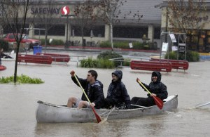 People canoeing in a flooded Healdsburg, California, parking lot in December.  AP / Eric Risberg