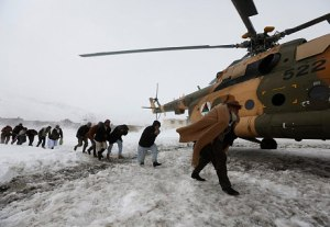 Survivors of an avalanche get relief goods distributed by an Afghan army helicopter (Reuters)