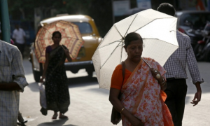 Indian commuters use umbrellas to stay cool in oppressive conditions. Photograph: Piyal Adhikary/EPA