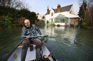 CHERTSEY, UNITED KINGDOM - JANUARY 08:  Ian Berry paddles a canoe through his front garden after the River Thames flooded on January 8, 2014 in Chersey, England. Parts of the United Kingdon are entering a third week of flooding and stormy conditions.  (Photo by Peter Macdiarmid/Getty Images)