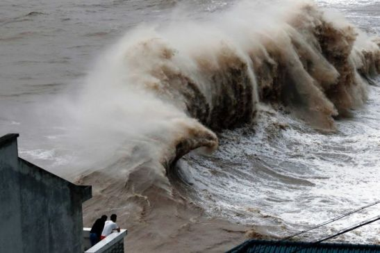 Photo: Two people watch huge waves from a balcony as Typhoon Chan-hom nears east China's Zhejiang province. (AFP