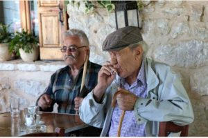Spyros Tsakiris / The associated press  Pensioner Panagiotis Theodoropoulos smokes a cigarette in a restaurant in the village of Karitaina on Thursday. Residents in that rural village are split on the value of membership in the eurozone, as many think the austerity measures imposed by the EU are unfair.