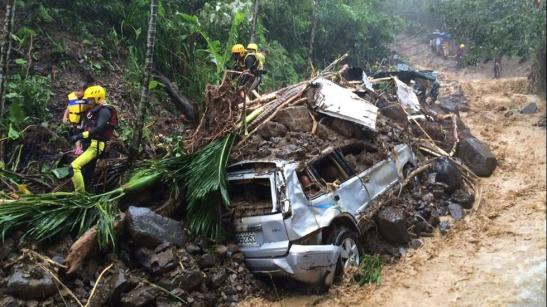 In this image released by the New Taipei Fire Department, emergency rescue personnel carrying children pass crushed cars from a flash mudslide caused by Typhoon Soudelor in Xindian, New Taipei City, northern Taiwan, Aug. 8, 2015. (New Taipei Fire Department via AP)
