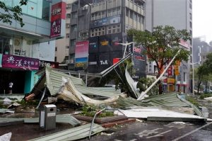 A street corner is filled with a mangled rooftop brought down by strong winds from Typhoon Soudelor in Taipei, Taiwan, Saturday, Aug. 8, 2015. Soudelor brought heavy rains and strong winds to the island Saturday with winds speeds over 170 km per hour (100 mph) and gusts over 200 km per hour (120 mph) according to Taiwan's Central Weather Bureau. (AP Photo/Wally Santana)