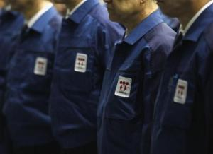 Logos of Tokyo Electric Power Co. (TEPCO), the operator of the tsunami-crippled Fukushima Daiichi nuclear plant, are seen on company uniforms as employees listen to a video speech by company president Naomi Hirose after taking part in a moment of silence at 2:46 p.m. local time (0546 GMT) at TEPCO's headquarters in Tokyo March 11, 2015, to mark the fourth anniversary of the March 11, 2011 earthquake and tsunami that killed thousands. REUTERS/Yuya Shino