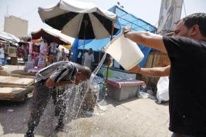 A man cools off during a warm summer day in Baghdad, July 30, 2015. A heat wave in the region, with the heat index in nearby Iran reaching up to 165 degrees Fahrenheit, has caused the Iraqi government to announce a four day public holiday.   Reuters