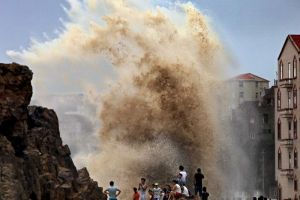 Photo: Residents gather to see huge waves stirred up by strong wind as Typhoon Soudelor draws near the mainland of China. (AFP: STR)