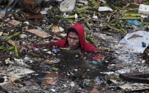 A man swims in polluted waters as he tries to salvage items from his house after two empty barges rammed into shanties on stilts at a poor community in Manila, Philippines Picture: AP Photo/Aaron Favila