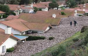 A TV news crew files a report behind damaged homes after a mud slide overtook at least 18 homes during heavy rains in Camarillo Springs, California December 12, 2014. JONATHAN ALCORN / Reuters
