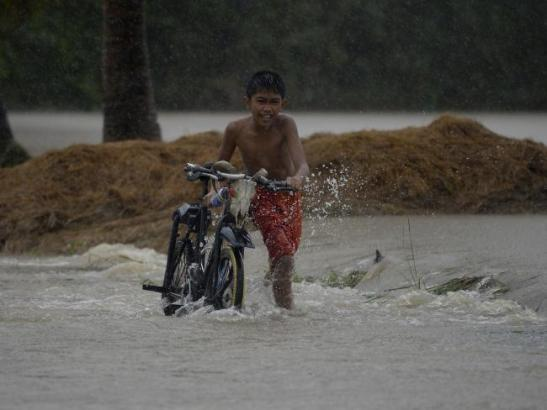 Inundated ... a child pushes his bicycle through a flooded street in Ineangan, Bambang, Nueva Viscaya. Picture: AFPSource:AFP Source: http://www.news.com.au/world/asia/deadly-typhoon-koppu-hits-the-philippines/story-fnh81fz8-1227573064068