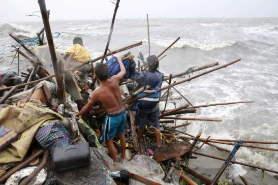 Photo: A family living along the coast of Manila Bay searches for salvageable items after their house was damaged by Typhoon Koppu. (Reuters: Romeo Ranoco)