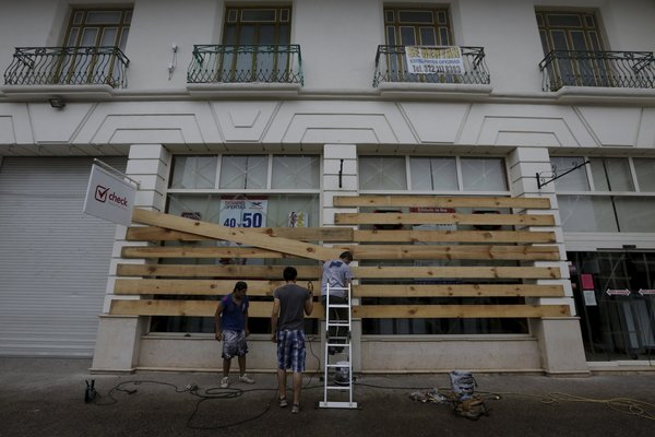 An employee boarded up a store in the Pacific coastal resort of Puerto Vallarta on Friday. The rapid strengthening of the storm caught many people off guard. Credit Henry Romero/Reuters