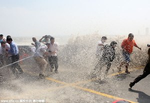 Powerful waves roar over a barrier, scaring spectators along the Qiantang River in Hangzhou, Zhejiang province, Sept 28, 2015. [Photo/IC] Image source: http://www.chinadaily.com.cn/china/2015-09/28/content_22001522.htm