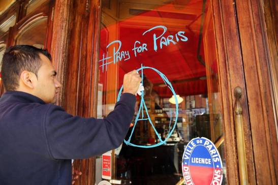 Employee Oscar Castillo draws a tribute to Paris on the door of the Brooklyn French restaurant Bar Tabac the day after the terrorist attack.  Photo:  Spencer Platt/Getty Images