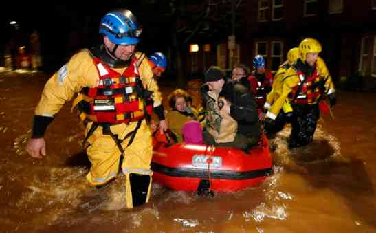 A family and their dog are rescued by the coastguard on Warwick Road in the centre of Carlisle after heavy rain from Storm Desmond tore through Britain, bringing strong winds and heavy rain which caused Cumbria to declare a major incident.. Picture date: Sunday December 6, 2015. The Environment Agency declared 130 flood warnings, while residents in some areas were evacuated from their homes. Rain continued to fall overnight in Scotland, northern England and northern parts of Wales, and is likely to continue for a few hours yet, forecasters said.See PA story WEATHER Winter. Photo credit should read: Owen Humphreys/PA Wire