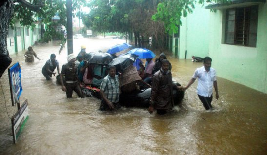 Indian rescue workers and volunteers use an inflatable boat to take residents through floodwaters in Chennai on December 1, 2015, during a downpour of heavy rain in the southern Indian city.  Heavy rains pounded several parts of the southern Indian state of Tamil Nadu and inundating most areas of Chennai, severely disrupting flights, train and bus services and forcing the postponment of half-yearly school exams.   AFP PHOTO/STR / AFP / STRDEL        (Photo credit should read STRDEL/AFP/Getty Images)