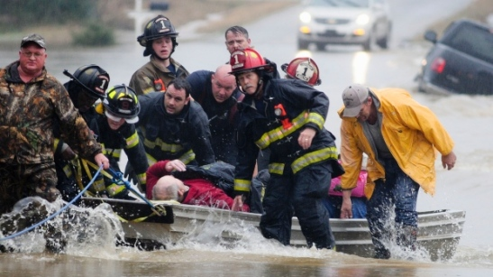 Emergency officials transport James Simmons by boat because water over Byler Road prevented them from reaching him in Moulton, Ala., Friday, Dec. 25, 2015. (Deangelo McDaniel/The Decatur Daily via AP)