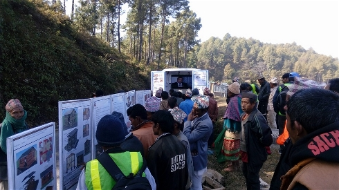 """Nepalis receive information in late 2015 about safely rebuilding homes via a """"mobile video van"""" provided by the United Nations Development Program"""