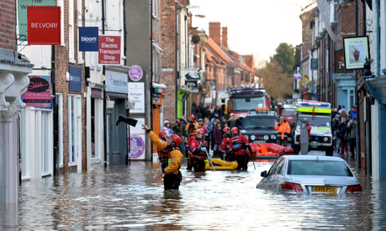 A rescuer throws a Wellington boot to a trapped resident in Walmgate, York, after the rivers Foss and Ouse burst their banks. Photograph: PA