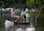 Residents sit on a bench at a flooded public square after a rainstorm in Buenos Aires in 2013. Photograph: Enrique Marcarian/Reuters